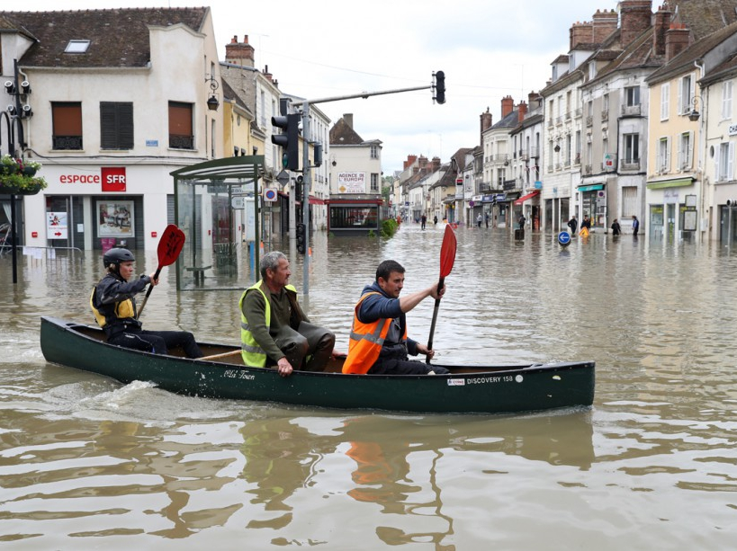 People paddle in a craft in a flooded street on June 1, 2016 in Nemours. Torrential downpours have lashed parts of northern Europe in recent days, leaving four dead in Germany, breaching the banks of the Seine in Paris and flooding rural roads and villages. / AFP PHOTO / KENZO TRIBOUILLARD